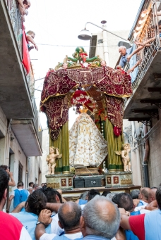 I portatori, senza alcuna sosta, trasferiscono la Madonna dalla chiesa di Sant'Agostino fino al piano della Madrice, attraverso le anguste strade di Caltabellotta. Queste permettono alle persone sui balconi di sfiorare con le loro mani la vara. The bearers, without any rest, transfer the statue of Mary from the church of Saint Augustine to the plain of the Mother Church, through the narrow streets of Caltabellotta. These let the people on the balconies to almost touch with their hands the vara.