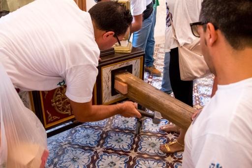Uno dei portatori fissa le travi alla vara per portarla in processione. - One of the bearers secures the beams to the vara to carry it into procession.