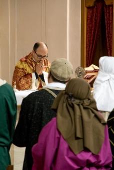 Padre Antonio Corda durante la celebrazione eucaristica della domenica delle palme con, in primo piano, coloro che intepretano i ruoli degli Apostoli e del popolo di Gerusalemme.