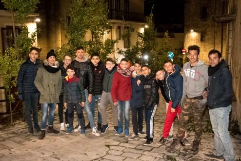 Una foto di gruppo dei ragazzi e membri del comitato impegnati nell'addobbare la città con le cime di alloro.