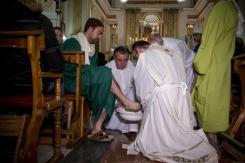 Padre Antonio Corda, come Gesù, lava con l'aiuto dei ministranti, i piedi di coloro che interpretano i ruoli degli Apostoli.