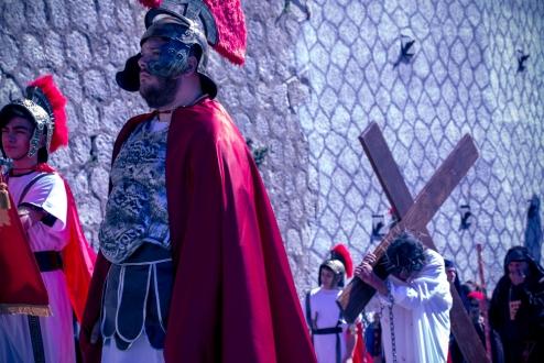 Gesù, scortato dalle guardie romane, porta la sua croce.
